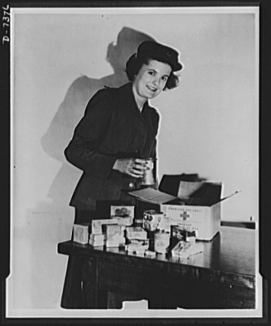 Packages for prisoners of war and internees. A Red Cross Canteen worker, Miss Mary Dougherty, inspects a Red Cross food package going to an American prisoner of war. Packages like this are sent regularly from International Red Cross headquarters in Geneva to American prisoners of war and interned civilians held by Germany and Italy. One a week goes to each American prisoner of war whose capture and location have been reported and one every two weeks to each interned civilian. Twenty thousand such packages were sent to the Far East on the neutral diplomatic exchange ship Gripsholm last June, together with one million cigarettes and other supplies for American prisoners and internees in Japan, occupied China and the Philippines. Much larger quantities are now on the Gripsholm pending final clearance with the Japanese for her sailing on a second trip