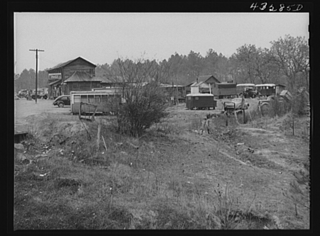 Part of a trailer camp for migratory workers, employed at Fort Bragg, North Carolina. Trailer space is one dollar a week, and small bunk houses five dollars a week. One water spigot near the general store serves the whole camp until 6 p.m. On the left is an old trolley car used as living quarters by a small family who came one hundred miles to work at the Fort. Some of the families here came from Texas, Idaho, Georgia, South Carolina and other parts of North Carolina twelve miles from Fayetteville, North Carolina (Manchester)