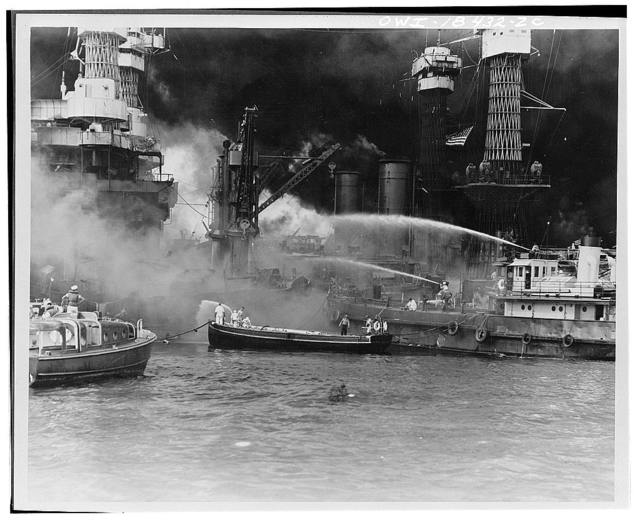 Pearl Harbor, Hawaii. USS West Virginia aflame.  Disregarding the dangerous possibilities of explosions, United States sailors man their boats at the side of the burning battleship, USS West Virginia, to better fight the flames started by Japanese torpedoes and bombs. Note the national colors flying against the smoke-blackened sky