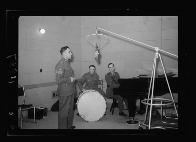 Photo taken in Palestine Broadcasting Service Studios, Jerusalem. Corporal at microphone, Cpl. Walters & Lt. Watson