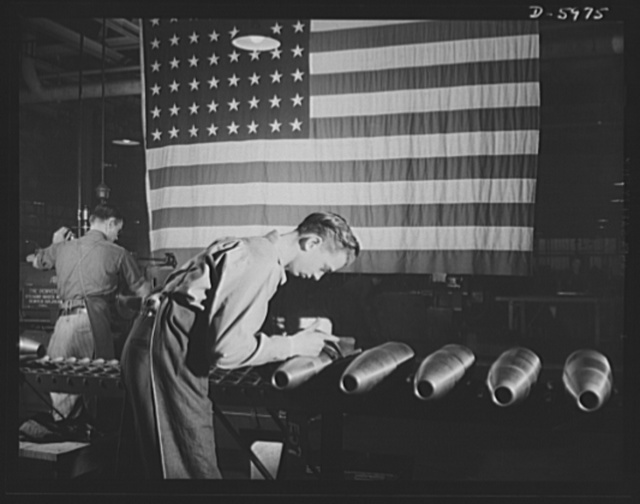 Production. 155mm shells. A government inspector checks 155mm shells after the finish turning of straight and profile diameters in a large converted auto plant. Willy's, Toledo, Ohio