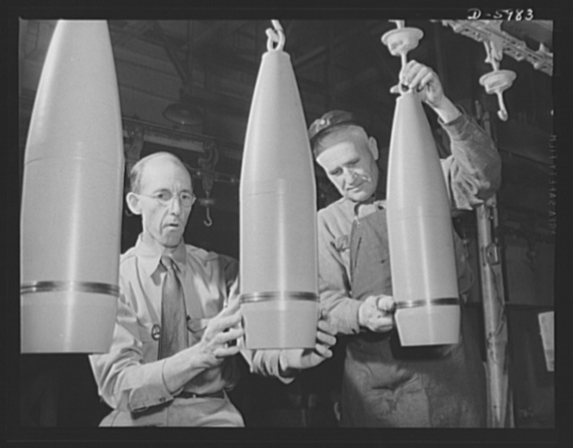 Production. 155mm shells. Government inspectors check the painting of 155mm shells as they pass by on the overhead drying conveyor of a converted auto plant. Willy's, Toledo, Ohio