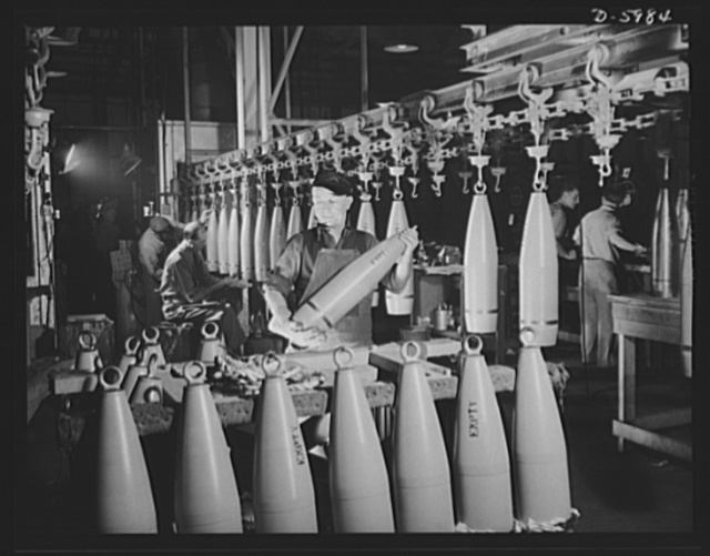 Production. 155mm shells. Unloading completed 155mm shell bodies from an overhead drying conveyor at a converted Midwest auto plant. Willy's, Toledo, Ohio