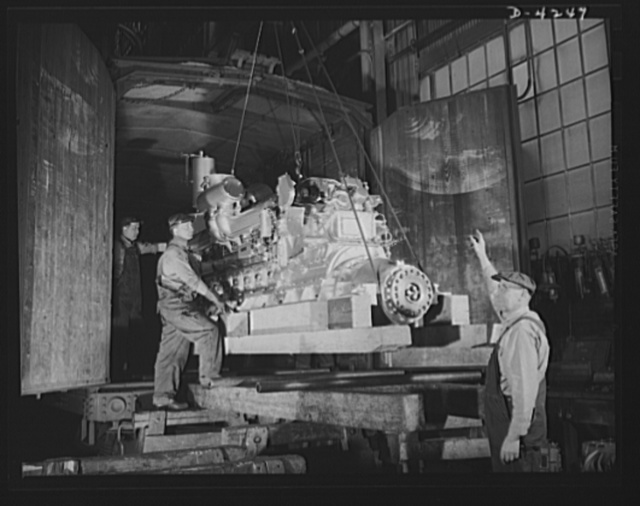 Production. Diesel engines. More power for the Navy. A diesel engine is loaded into a railroad car for shipment from a Midwest manufacturing plant