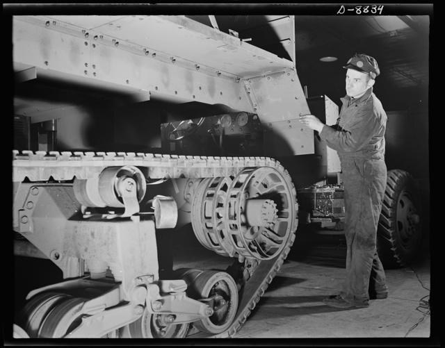 Production. Halftrac armoured cars. A partly-finished halftrac scout car body is lowered on a chassis in an Eastern war plant which formerly produced locks and safes. Diebold Safe and Lock Company, Canton, Ohio