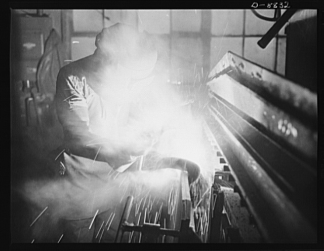 Production. Halftrac armoured cars. An arc welder joins parts of the body of a halftrac scout car in the converted Eastern plant of a lock and safe manufacturer. Diebold Safe and Lock Company, Canton, Ohio