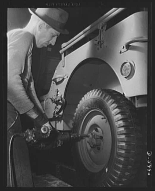 """Production. Jeeps. Putting """"shoes"""" on another hard-boiled recruit. An army jeep nears completion in a big Midwest auto plant. Willy's, Toledo, Ohio"""