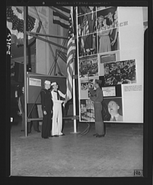 Protectors of the Four Freedoms raise Old Glory by the Office of Emergency Management's (OEM) huge Four Freedoms photomontage at the National and Civilian Defense Exposition in Grand Central Palace, New York. This panel, which measures 15 x 30 feet, and another of equal size entitled Arsenal of Democracy were designed by Jean Carlu, eminent poster artist, in accordance with a new technic in montage used only once before. The sections are 2 1/2 feet square. The panels will shortly be seen in a number of other cities