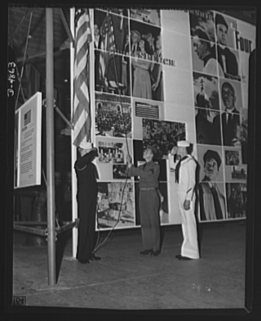 Protectors of the Four Freedoms raise Old Glory by the Office of Emergency Management's huge Four Freedoms montage at the Natinoal Civilian and Defense Exposition in Grand Central Palace, New York. This panel, which measures 15 x 30 feet, and another of equal size entitled Arsenal of Democracy, were designed by Jean Carlu, eminent poster artist, in accordance with a new technique in montage used only once before.