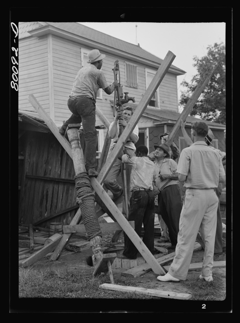 Pump is lowered on pump rod and casing before settling drop pipe in place. Long well project, Saint Mary's County, Maryland