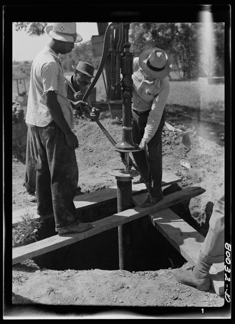 Pump is settled onto pump rod and drop pipe. Pipe wrench still keeps drop pipe from slipping into well. John Fredrick well project, St. Marys County, Maryland