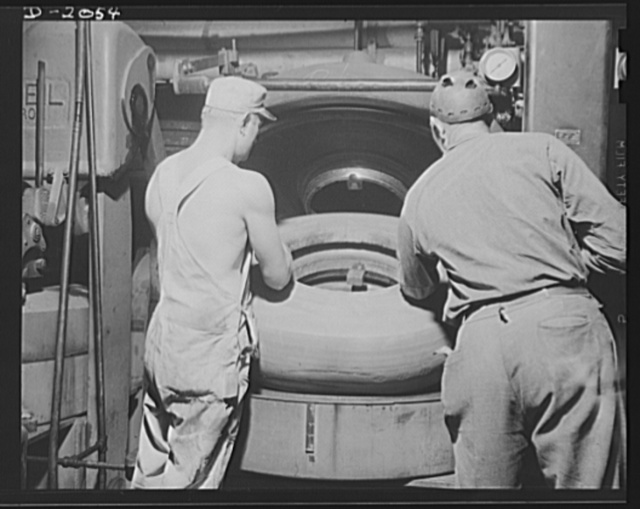 """Putting tire into curing mold. From the vacuum expander, the potential new truck tire is taken to this """"watch-case"""" curing mold in which it is baked under high heat and pressure for a long time. The exact time and temperature varies with the type and size of tire. The airbag inside the carcass is filled with live steam during this process so that heat is added from both inside and out. The mold contains the tread pattern, or design, as well as all markings which will appear on sidewall. Under this heat and pressure the rubber turns semi-liquid, and flows into every crevice, completely bonding the rubber processed fabric carcass to the cushion, the cushion to the tread. After this operation it is now one unit--a complete tire. Firestone (General) Tires, Akron, Ohio"""