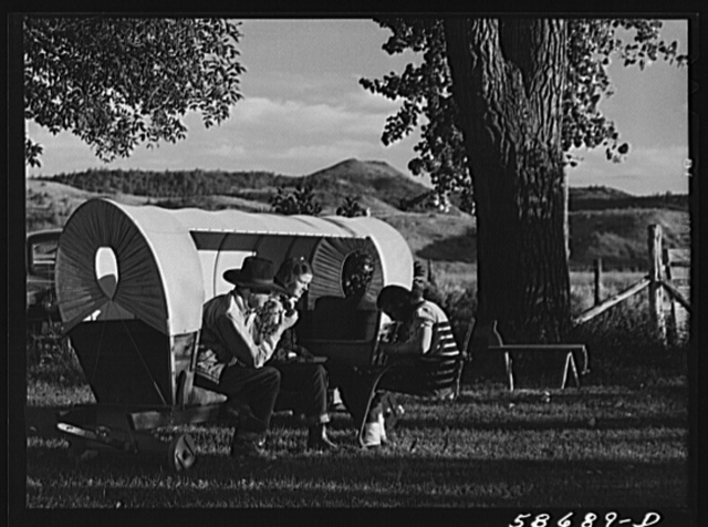 Quarter Circle U, Brewster-Arnold Ranch. Birney, Montana. Dudes in a covered wagon garden seat.