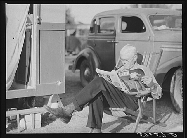 Reading magazine beside his trailer home. Sarasota trailer park, Sarasota, Florida