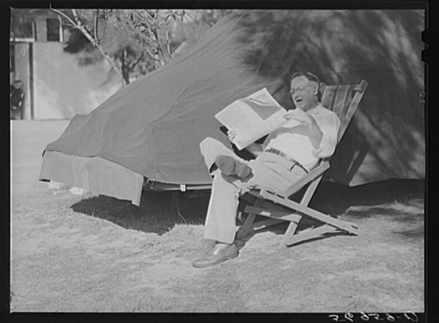 Reading newspaper. Sarasota trailer park, Sarasota, Florida