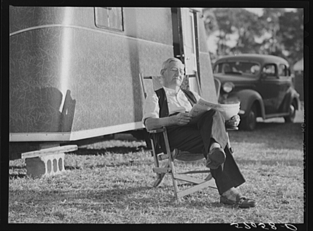 Reading the newspaper outside his trailer home. Sarasota trailer park, Sarasota, Florida