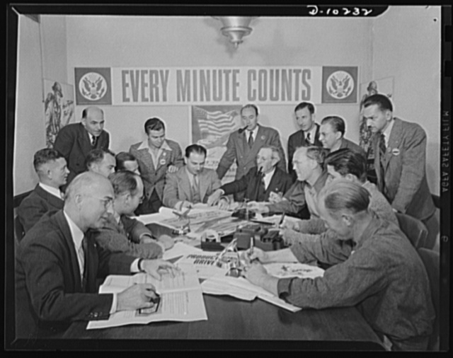 Regular meeting of the Employee-Management Production Drive Committee at the Santa Monica, California plant of Douglas Aircraft Company, Inc. Looking over the shoulder of factory manager, Henry Guerin, left center, is Victor Ferris, youthful worker in the final assembly department. In this aircraft plant, one of the world's largest, there is a fine spirit of cooperation between labor and management
