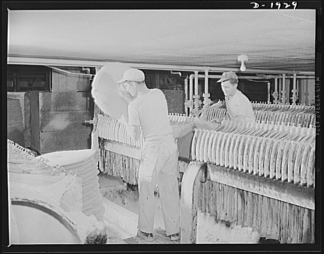 Removing cakes of clay from one of a battery of filter presses. This operation precedes the pug mill. Shenango Pottery Works, Newcastle, Pennsylvania