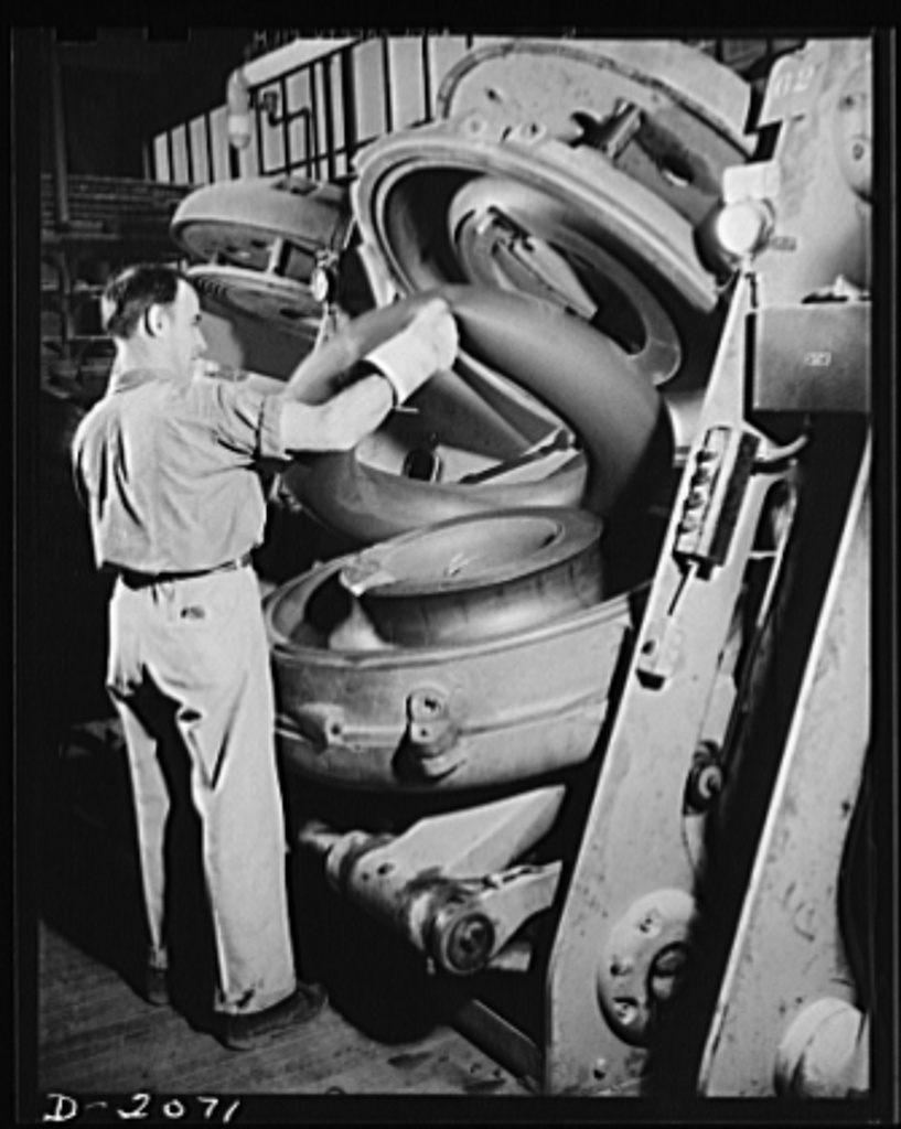 Removing cured tube from mold. As the tire molds are all-automatic, so are the tube molds. This one has just opened; all the operator need do is remove the finished tube and put in another raw one. Note the seam marks in the mold itself, which leave their imprint on the tube. Thus a seamless tube may appear to have a collection of many sections. Firestone (General) Tires, Akron, Ohio