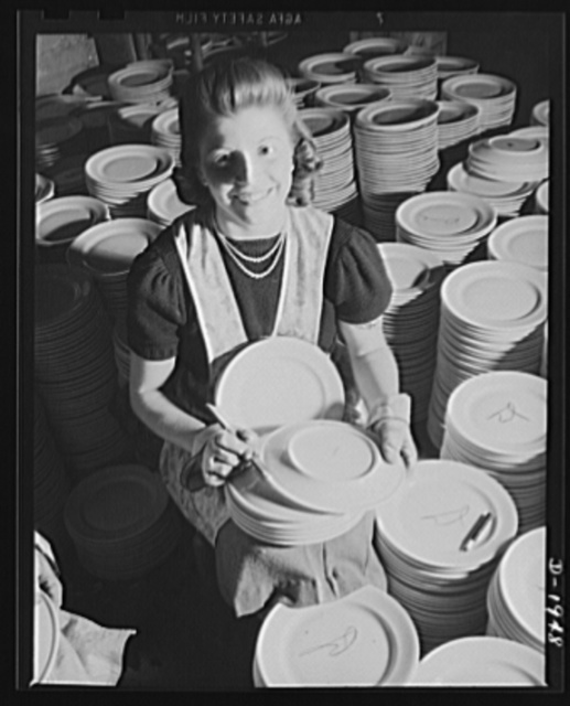 Removing firing marks from the backs of dinner plates for the crew's mess of the Navy. Shenango Pottery Works, Newcastle, Pennsylvania