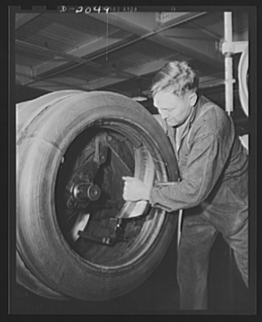 Removing the finished tire from the tire drum. The inner drum shoes are unlocked after the tire is loosened; They are removed, leaving the tire free to slide right off. Then they are replaced and the next tire is started. Firestone (General Tires), Akron, Ohio