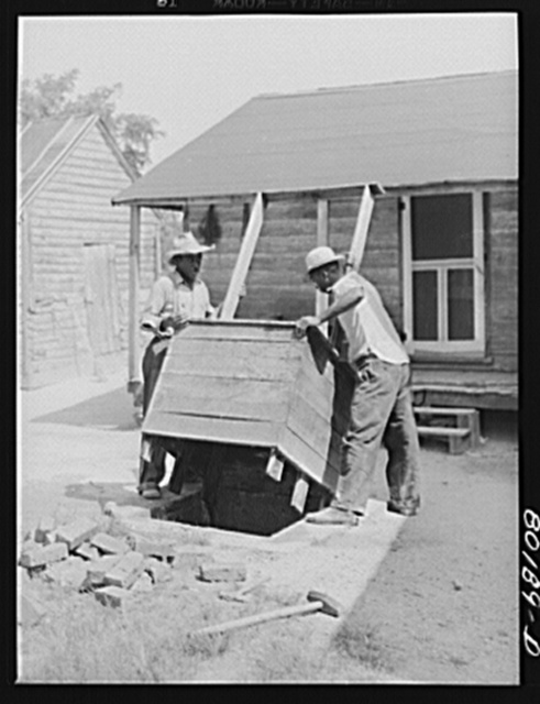 Removing the old wooden box from the top. Safe well demonstration near La Plata, Maryland. Charles County