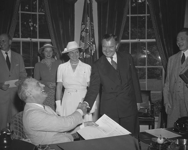 Robert Jackson sworn in as Justice. Washington, D.C. July 11. Robert Jackson was sworn in as Associate Justice of the Supreme Court in President Roosevelt's office before an audience comprising most of the high officials of the New Deal with whom he had been associated for seven years. Picture shows the President as he congratulates Jackson. Left to right--Mary Jackson, daughter of Mr. Jackson, Mrs. Jackson and Robert Jackson. President Roosevelt is in left foreground