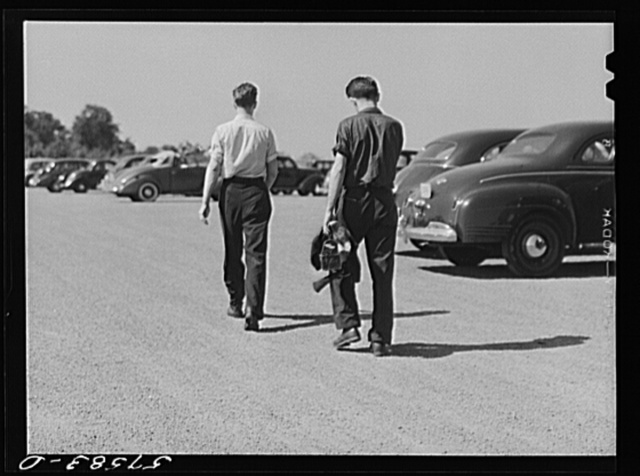 Rolfe Chickering, farmboy from Saint Johnsbury, Vermont, leaving work at Pratt and Whitney United Aircraft with his friend. They commute to Suffield, Connecticut because of housing congestion around East Hartford, Connecticut (see 57612D)