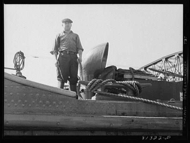 Sailor slacking of ship's hawser as vessel settles in Lock Eleven. Amsterdam, New York