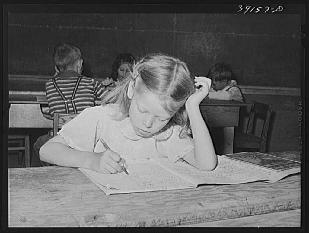 Schoolgirl at the FSA (Farm Security Administration) farm workers' camp. Caldwell, Idaho. Several family units of the row shelters have been thrown open to form a big room for the school