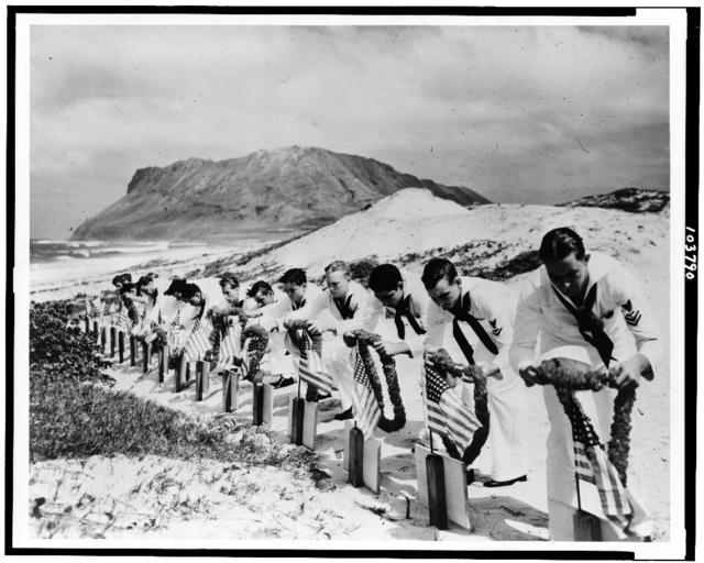 Seamen at Kaneohe Naval Air Station decorate the graves of their fellow sailors killed at Pearl Harbor, December 7, 1941 / Official U.S. Navy photograph.
