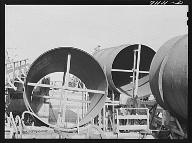 Segments of penstock pipe which will be used to transport water from reservoir formed by Shasta Dam to hydroelectric turbines. Notice the worker on top pipe; he is welding segments together. Shasta County, California