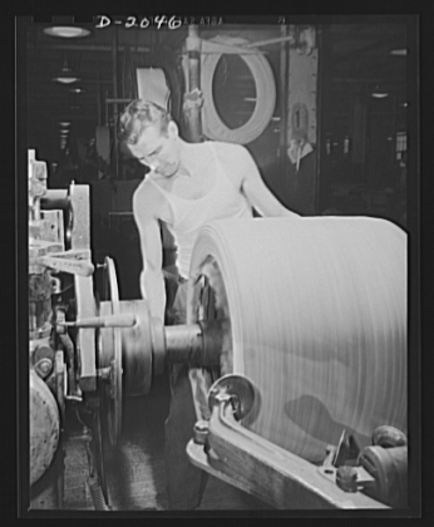 "Shaping the tire with ""saucers."" Spinning discs which are delicately controlled by movable arms smooth out each layer of fabric as it is added to the growing carcass, and curves around the sidewall and bead with considerable pressure. In the center foreground, one of these saucers may be seen as this tire builder maneuvers it around the sharp corner of the tire drum. In the right foreground two others pull across from the center to the edges to smooth out each layer. Firestone (General Tires), Akron, Ohio"
