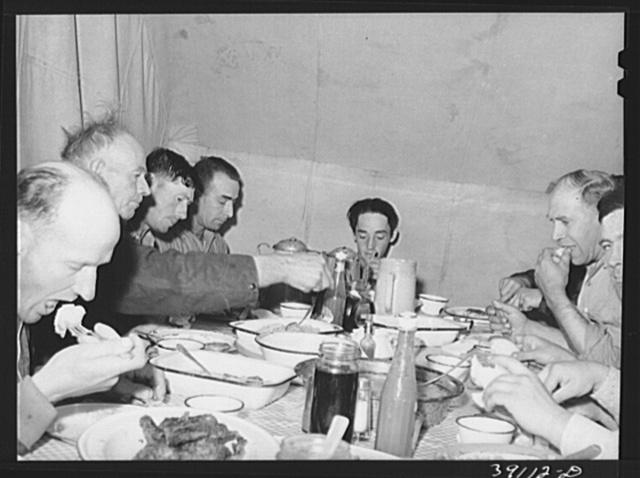 Sheep shearers eating dinner in central tent. Ranch in Malheur County, Oregon. The wife of the owner and boss of the outfit does the kraut and ham, dried beans, canned tomatoes, potatoes, pudding, jams and jellies, coffee and tea