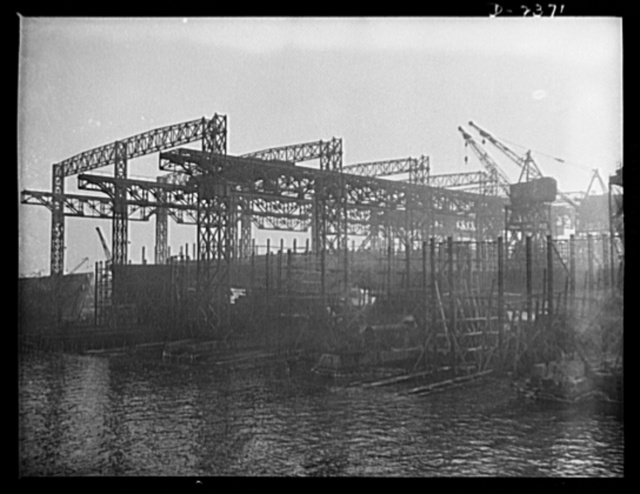 "Shipbuilding. ""Liberty"" ships. A view from the water of the shipways at a large Eastern yard. At the left is seen the old-style superstructure, with tracks for two-way overhead cranes, while at the right, running on ground tracks, are the more modern cranes, designed for hoisting from any angle. Bethlehem-Fairfield Shipyards Inc., Baltimore, Maryland"