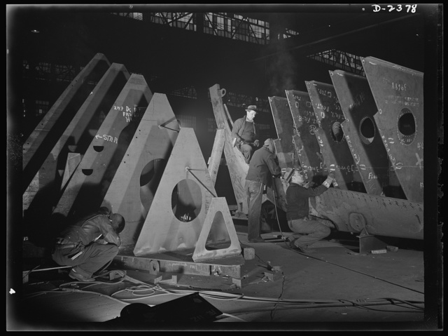 """Shipbuilding. """"Liberty"""" ships. In an abandoned freight car factory near the Atlantic coast, sections of sleek freighters for the merchant fleet are being prefabricated. Present rate of production is one a week. The men shown at work here believe they can increase that rate to one in six days"""