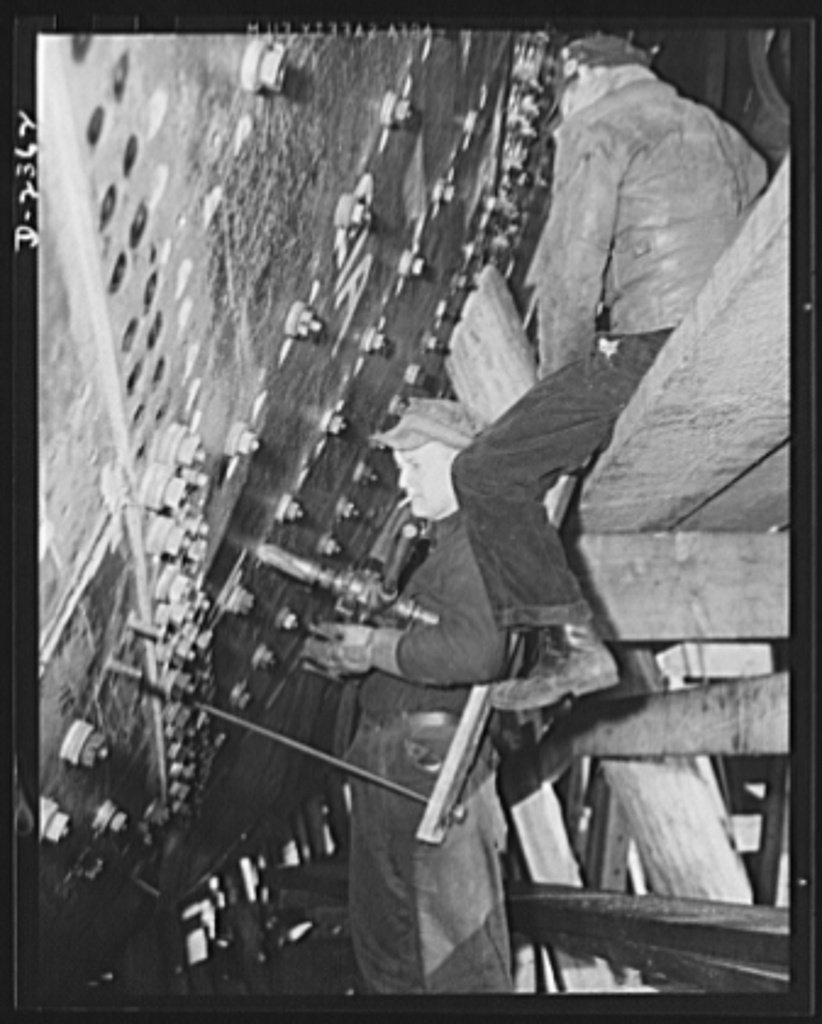 "Shipbuilding. ""Liberty"" ships. Shell plates of a ship at the bow, where the inner plates are first bolted to the outer plates for added strength. The rivets are countersunk to be flush on the outer side. Production scene in a large Eastern shipyard. Bethlehem-Fairfield Shipyards Inc., Baltimore, Maryland"