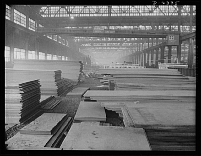 "Shipbuilding. ""Liberty"" ships. Steel plates of wasteless dimensions stacked ready for laying out, one of the first operations on the production line of multiply cargo ship construction. All parts are prefabricated in this huge Eastern plant which formerly turned out freight cars. The completed sections are then carried six miles to the ways on flat cars. Bethlehem-Fairfield Shipyards Inc., Baltimore, Maryland"