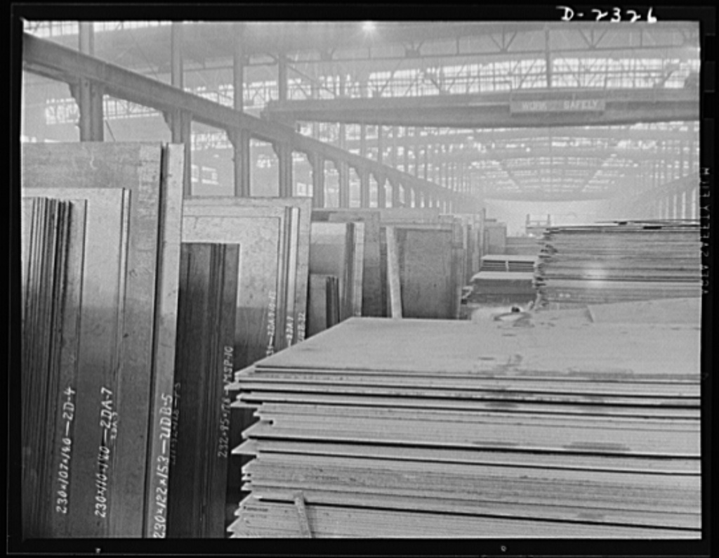 """Shipbuilding. """"Liberty"""" ships. These stacks of steel plate are in readiness for an uninterrupted flow toward the production line of a large Eastern plant fabricating sections for ships built at a nearby yard. This plant was formerly used for Pullman car construction. Bethlehem-Fairfield Shipyards Inc., Baltimore, Maryland"""