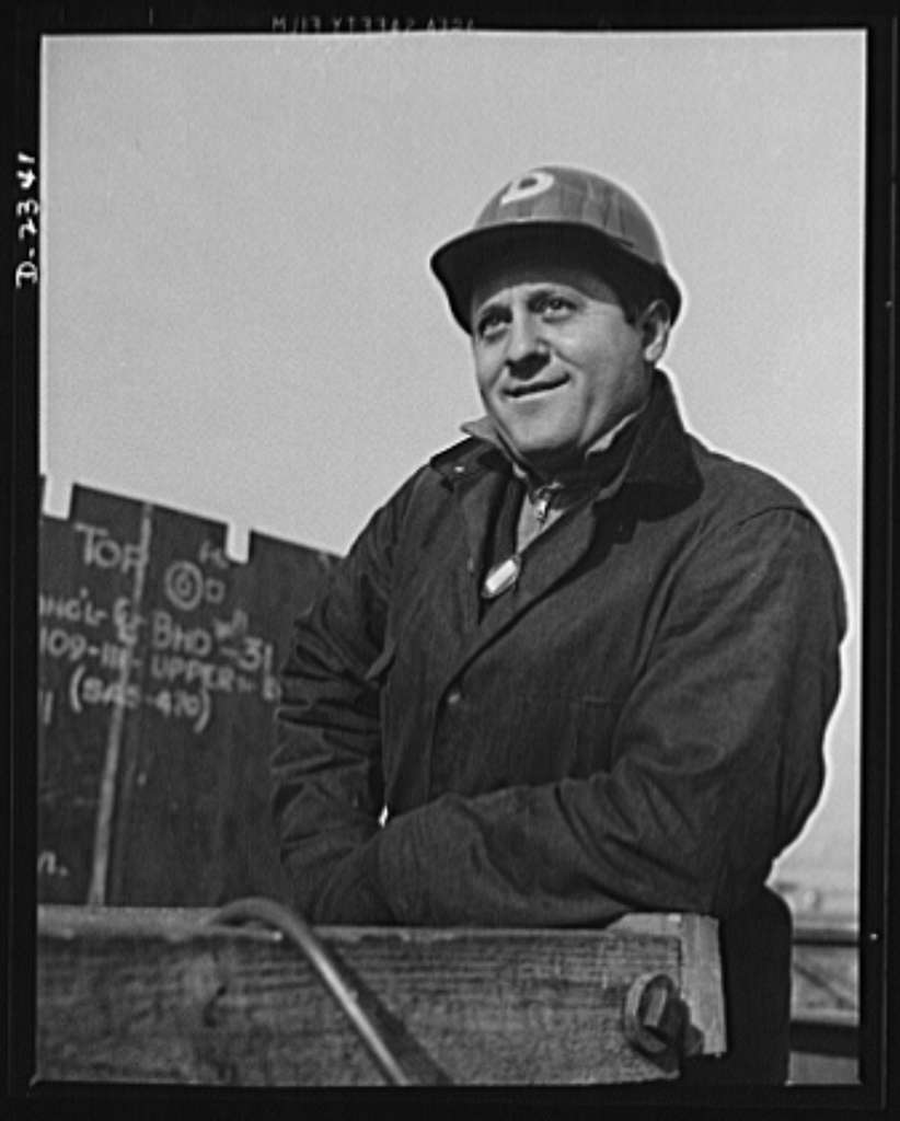 """Shipbuilding. """"Liberty"""" ships. This is the signal man of a riggers crew at a large Eastern shipyard. He is about ready to give the go-ahead signal to the operator of a large overhead electric crane. Bethlehem-Fairfield Shipyards Inc., Baltimore, Maryland"""