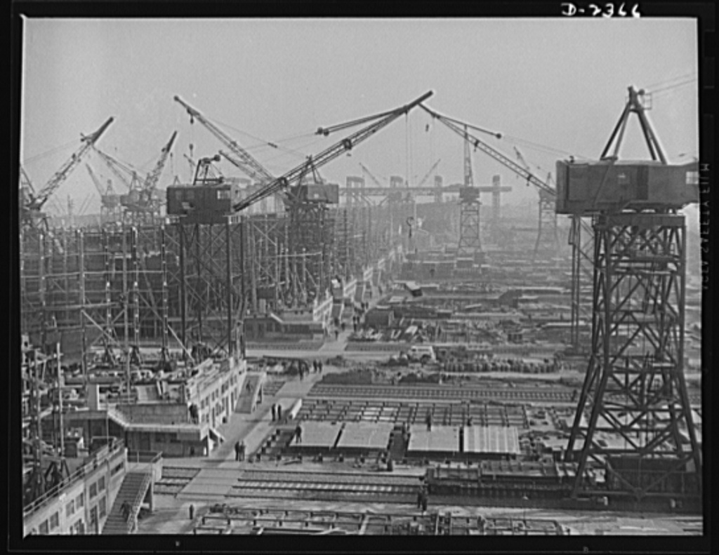 """Shipbuilding. """"Liberty"""" ships. This maze of rolling cranes, at a large Eastern shipyard is a typical scene in many large shipyards at work on ships for Uncle Sam's Navy and merchant fleet. Stocks of material are piled up for the cranes to take to vessels under construction so there is no delay in production while waiting for sections or materials. All parts are prefabricated in this huge Eastern plant which formerly turned out freight cars. The completed sections are then carried six miles to the ways on flat cars. Bethlehem-Fairfield Shipyards Inc., Baltimore, Maryland"""