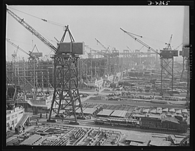 """Shipbuilding. """"Liberty"""" ships. This maze of rolling cranes, at a large Eastern shipyard is a typical scene in many large shipyards at work on ships for Uncle Sam's Navy and merchant fleet. Stocks of material are piled up for the cranes to take to vessels under construction so there is no delay in production while waiting for sections or materials. All parts are prefabricated in this Eastern plant which formerly turned out freight cars. The completed sections are then carried six miles to the ways on flat cars. Bethlehem-Fairfield Shipyards Inc., Baltimore, Maryland"""