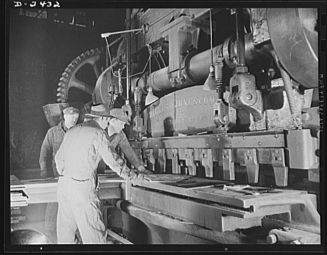 """Shipbuilding. """"Liberty"""" ships. Workers at a prefabricating plant turn out steel parts for a large Eastern shipyard building units of Uncle Sam's """"Liberty Fleet."""" Here they operate a giant shear. This plant was originally used to produce freight cars, and the shears are part of the plant's original equipment. All parts are prefabricated in this huge Eastern plant which formerly turned out freight cars. The completed sections are then carried six miles to the ways on flatcars. Bethlehem-Fairfield Shipyards Inc., Baltimore, Maryland"""