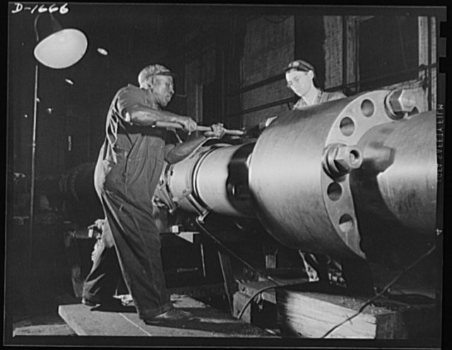 Shipbuilding (Newport News). Skilled work requires brawn as well as brains. This husky navy yard worker is driving home a pin in the propeller shaft of a naval vessel under construction