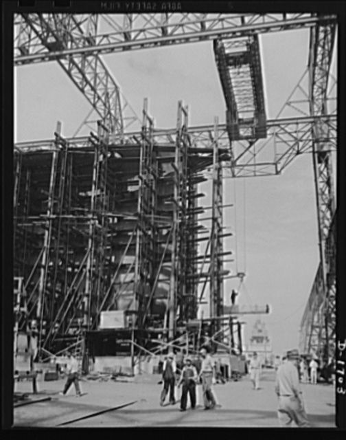 Shipbuilding (Newport News). Through the scaffolding may be seen the prow of a battleship under construction. The Norfolk-Newport News section of Virginia is contributing a large portion of the new tonnage of our rapidly expanding two-ocean Navy