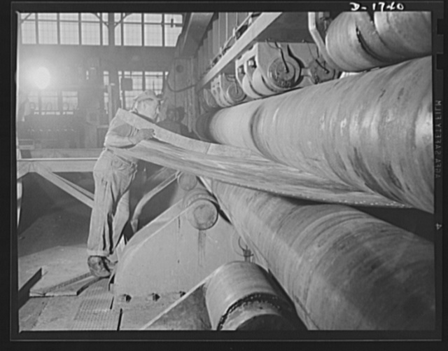 """Shipbuilding (Norfolk Navy Yard). Tedious and exacting is the work of this highly skilled machinist. He is shaping a ship's plate, a difficult operation which must be accurate to the """"nth"""" degree"""
