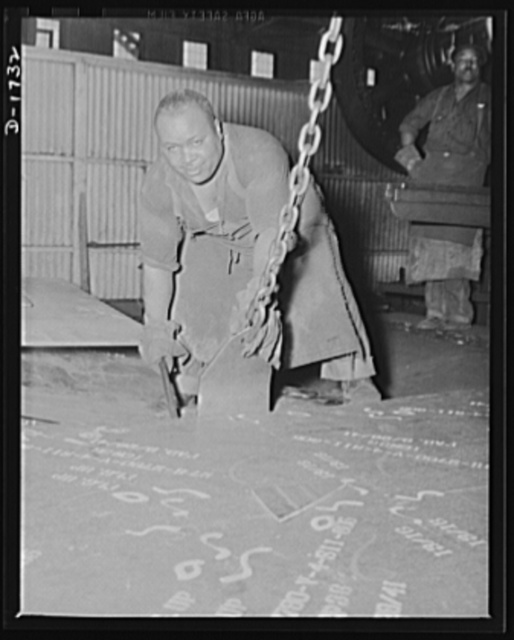 Shipbuilding (Norfolk Navy Yard). This worker is in the plate-bender's shop, where steel plates are bent to fit the sidings of warcraft under construction. This is an operation requiring a high degree of skill