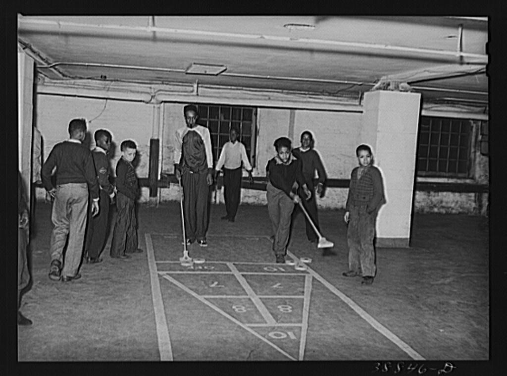 Shuffleboard being played in basement of Good Shepherd Community Center. Chicago, Illinois