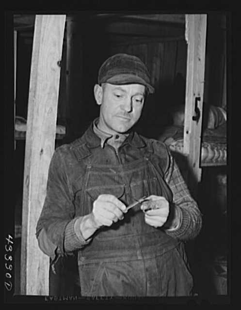 Silver Lake (vicinity), North Carolina. A worker who is employed at Fort Bragg in the doorway of a bunkerhouse in which he rents a lower berth