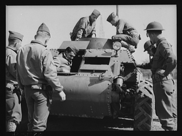 Soldiers inspecting new trackless tank during demonstration at Fort Myer, Virginia. Tank was manufactured by the Trackless Tank Corporation of New York, and submitted to the Ordnance Department, U.S. Army, for inspection. Preliminary tests indicate that the tank may be adaptable for reconnaissance purposes, possibly replacing scout cars. Tank weighs 10 tons. During initial, brief tests at Fort Knox, Kentucky, it made 45 miles an hour across rough country, with a 37 mm gun and two machine guns mounted in its turret; its designer says it can travel 85 mph on level ground. It is powered by a 250 horsepower diesel engine, and carries 1/2-inch armor. Tentative plans of the Army call for a redesign of the superstructure for better arming of the tank